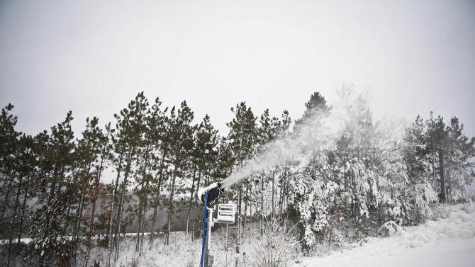 Snow blowers funnel snow onto Cannonsburg's main runs during Cannonsburg Ski Hill's opening day on Wednesday, Dec. 26, 2012 in Belmont, Mich. (AP Photo/The Grand Rapids Press, Matthew Busch)