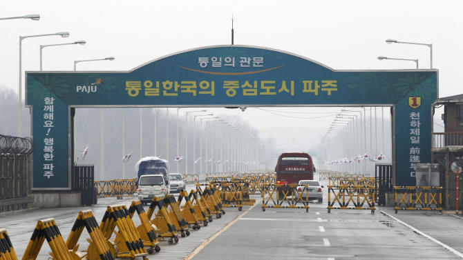 "South Korean vehicles, left, return from the North Korean city of Kaesong at Unification Bridge in Paju, South Korea, near the border village of Panmunjom, Saturday, April 6, 2013. More South Koreans on Saturday began to leave North Korea and the factory park where they work, four days after Pyongyang closed the border to people and goods. The letters read "" Unification Gate."" (AP Photo/AhnnYoung-joon)"