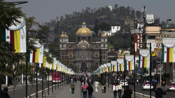 Signs welcoming Pope Francis decorate the walkway leading to the Basilica of Guadalupe in Mexico City, Thursday, Feb. 11, 2016. The pontiff arrives in Mexico on Friday for a week-long visit. (AP Photo/Marco Ugarte)