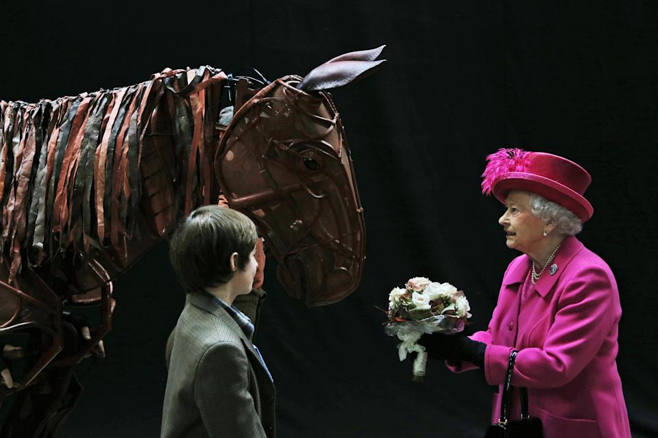 Britain's Queen Elizabeth II receives flowers from a child actor as she inspects the horse prop from the theatre production 'War Horse' during a visit at the National Theatre in London, Tuesday Oct. 22, 2013 to commemorate the institution's 50th anniversary. (AP Photo/Lefteris Pitarakis, pool)