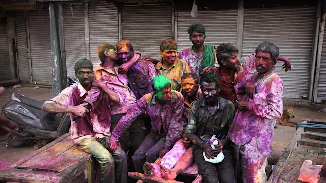 """Indian laborers smeared with colors have a light moment as they celebrate """"Holi,"""" the festival of colors in New Delhi, India , Wednesday, March 27, 2013. Holi is an ancient and the most popular Hindu festival here to celebrate the arrival of spring among Indians across the country. (AP Photo /Manish Swarup)"""