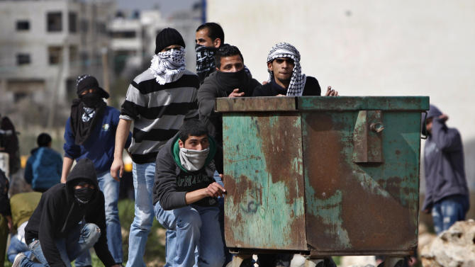 Palestinians take cover during clashes with Israeli troops, outside Ofer, an Israeli military prison near the West Bank city of Ramallah, Friday, Feb. 15, 2013. Palestinian demonstrators clashed with Israeli soldiers on Friday at a rally held in support of a prisoner observing an intermittent hunger strike to protest his incarceration. The Israeli military said about 200 Palestinians threw rocks at soldiers who responded with tear gas during the rally outside Ofer prison in the West Bank. The protesters called for the release of Samer Issawi, who has been on an on-again, off-again hunger strike for several months as he serves time for alleged terror activity. (AP Photo/Majdi Mohammed)