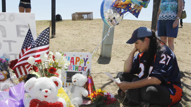 "Shelly Fradkin, the mother of a friend of shooting victim Alex Sullivan, looks at a birthday card for Sullivan placed at a makeshift memorial across from the Century 16 theatre east of the Aurora Mall in Aurora, Colo., on Saturday, July 21, 2012. Twelve people were killed and dozens were injured in the attack early Friday at the packed theater during a showing of the Batman movie, ""The Dark Knight Rises.""   Police have identified the suspected shooter as James Holmes, 24.  (AP Photo/David Zalubowski)"