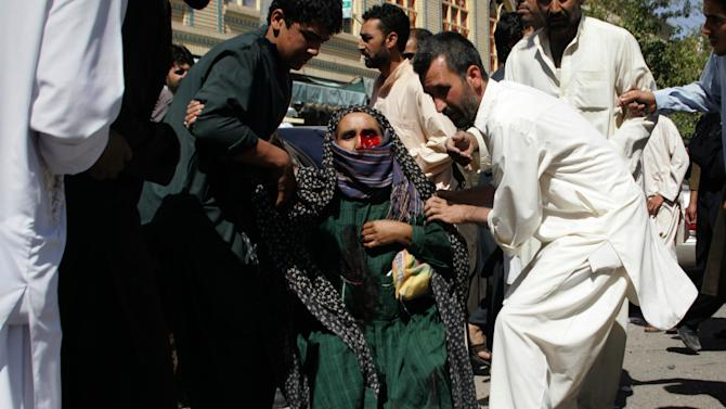 FILE - In this Wednesday, Aug. 15, 2012 file photo, Afghans carry a wounded woman from the scene of an explosion in Herat, west of Kabul, Afghanistan. A U.N. report says 1,145 civilians were killed and 1,954 others injured during the first half of the year, 80 percent of them by militants. But like other aspects of this decade-long war, facts are often obscured by perception and propaganda. That has left both sides locked in a battle of words, crafted to win the Afghan public's support. (AP Photo/Hoshang Hashimi, File)