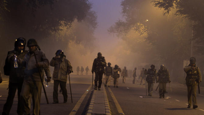 Indian policemen walk back after chasing away protestors during a violent protest in New Delhi, India, Sunday, Dec. 23, 2012. Police in India's capital used tear gas and water cannons for a second day Sunday in a high-security zone to break up protests by thousands of people demonstrating against the gang rape and beating of a 23-year-old student on a bus.(AP Photo/Altaf Qadri)