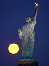 The moon rises near the Statue of Liberty as seen from Liberty State Park, Wednesday, June 15, 2011 in Jersey City, N.J. (AP Photo/Julio Cortez)