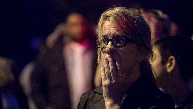 Mimi de Quesada, of Watertown, Mass., reacts while standing by her home in the wake of the sound of shots fired in Watertown, Mass., Friday, April 19, 2013, as a massive search continued for one of two suspects in the Boston Marathon bombings. De Quesada said she had just come out to enjoy the day when the shots rang out about two blocks form her home. A second suspect died in the early morning hours after an encounter with law enforcement. (AP Photo/Craig Ruttle)