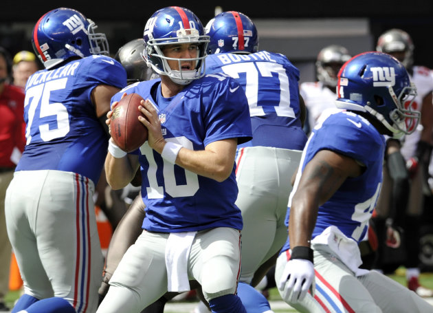 New York Giants quarterback Eli Manning (10) looks to pass as teammates Sean Locklear (75) and Kevin Boothe (77) block during the first half of an NFL football game against the Tampa Bay Buccaneers Sunday, Sept. 16, 2012, in East Rutherford, N.J. Manning threw for 510 yards, second most for a Giants quarterback, and Andre Brown's 2-yard run with 31 seconds left lifted New York to a wild 41-34 victory Sunday over the Tampa Bay Buccaneers. (AP Photo/Bill Kostroun)