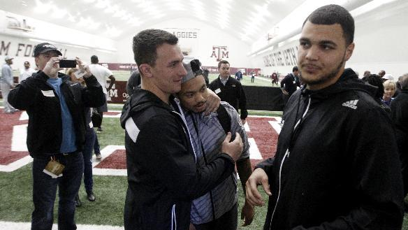 Texas A&M quarterback Johnny Manziel, left, gives receiver LaQuvionte Gonzalez a hug as receiver Mike Evans, right, walks by at the end of Texas A&M's pro day Wednesday, March 5, 2014, in College Station, Texas. Manziel and Evans did not compete
