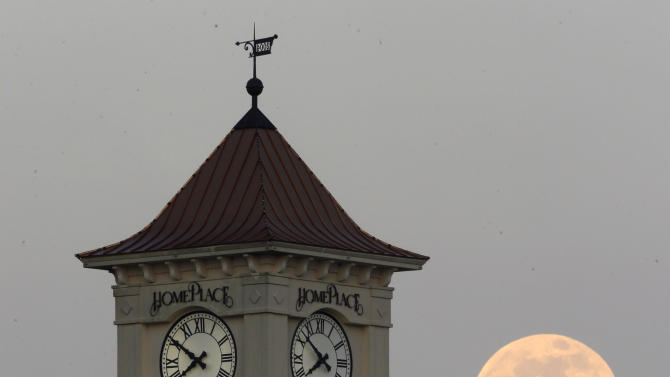 "A ""supermoon"" rises behind the Home Place clock tower in Prattville, Ala., Saturday, June 22, 2013. The biggest and brightest full moon of the year graces the sky early Sunday as our celestial neighbor swings closer to Earth than usual. While the moon will appear 14 percent larger than normal, sky watchers won't be able to notice the difference with the naked eye. Still, astronomers say it's worth looking up and appreciating the cosmos. (AP Photo/Dave Martin)"
