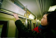 "FILE - In this Dec. 14, 1993 file photo, Carmen Rios of Staten Island, N.Y., reads John Keats' ""Ode To Autumn"" while riding in a New York City subway car. The MTA is eliminating its literary placards - quotes from thinkers like Kafka, Keats, Dante and Galileo - with messages informing customers on improvements in the transit system."
