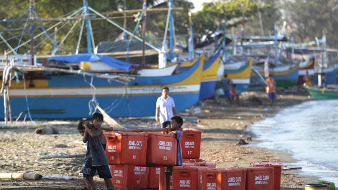 In this May 7, 2013 photo, Filipino boys carry empty containers for fish in the coastal town of Infanta, Pangasinan province, northwestern Philippines. Since China took control of the Scarborough Shoal last year, which Beijing calls Huangyan Island, Filipino fishermen say Chinese maritime surveillance ships have shooed them from the disputed waters in the South China Sea and roped off the entrance to the vast lagoon that had been their fishing paradise for decades, forcing many of them to sell their boats, or simply abandoned them on the coast, and turn to other work.  (AP Photo/Aaron Favila)