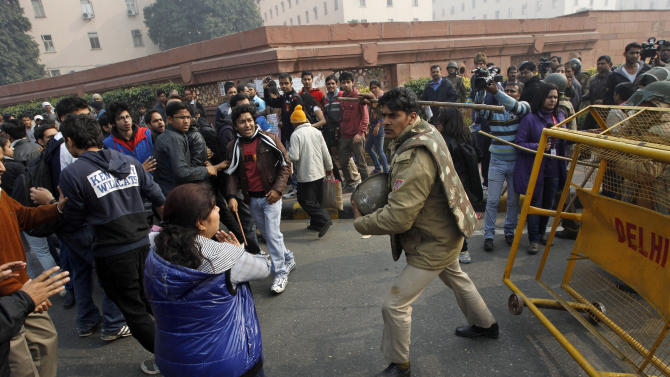 An Indian policeman baton charges to disperse protesters demonstrating against a gang rape and brutal beating of a 23-year-old student on a bus in New Delhi, India, Sunday, Dec. 23, 2012. The attack last Sunday has sparked days of protests across the country. (AP Photo/Tsering Topgyal)