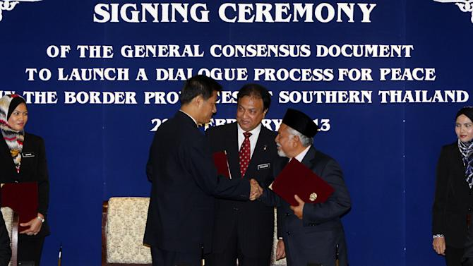 Thailand's National Security Council Secretary general Paradorn Pattanathabutr, second from left, and Malaysian-based National Revolution Front chief Hassan Taib, second from right, shake hands after exchanging signed documents as Malaysia's National Security Council Secretary Mohamed Thajudeen Abdul Wahab, center, witnesses during the signing ceremony of the general consensus document to launch a dialogue process for peace in the border provinces of southern Thailand, in Kuala Lumpur, Malaysia, Thursday, Feb. 28, 2013. Thai authorities and Muslim militant leaders based in neighboring Malaysia agreed Thursday to hold talks to help ease nearly a decade of unrest in southern Thailand. (AP Photo/Lai Seng Sin)
