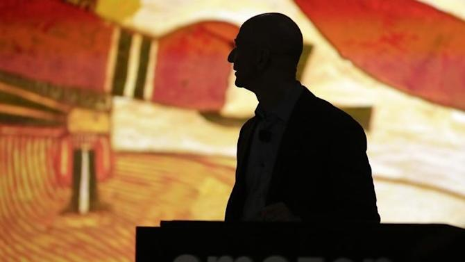 Amazon CEO Bezos is silhouetted during a presentation of his company's new Fire smartphone in Seattle