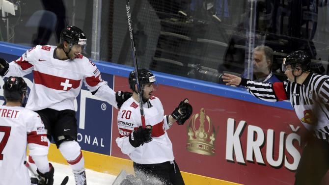 Switzerland's Hollenstein celebrates with his teammates Romy and Streit after scoring a goal against France during their Ice Hockey World Championship game at the O2 arena in Prague