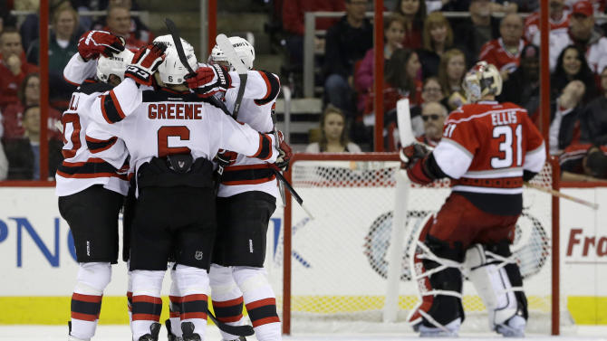 New Jersey Devils' Peter Harrold, left, Andy Greene (6) and Patrik Elias,  third from right, of the Czech Republic, celebrate Harrold's goal against Carolina Hurricanes goalie Dan Ellis (31) during the second period of an NHL hockey game in Raleigh, N.C., Thursday, March 21, 2013. (AP Photo/Gerry Broome)