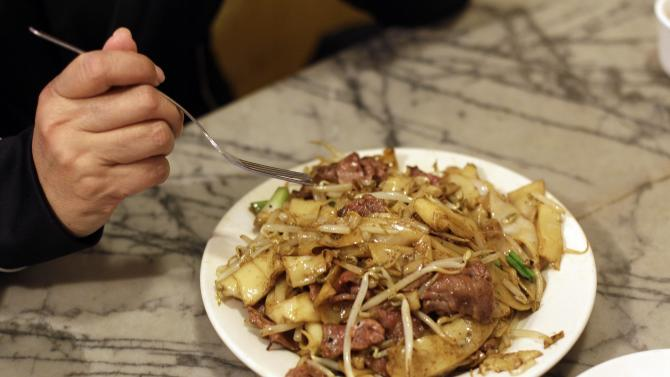 "A woman begins to eat a dish of beef chow fun for lunch at the Sam Wo restaurant in Chinatown in San Francisco, Friday, April 20, 2012. The 100-year-old Chinese restaurant known for having ""the world's rudest waiter"" is shutting its doors and serving its last customers Friday. (AP Photo/Eric Risberg)"
