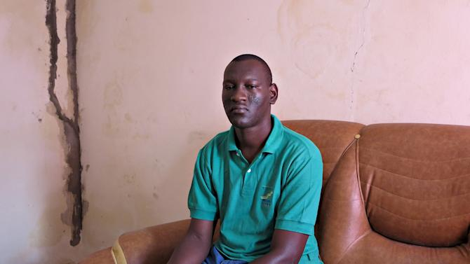 Mamadou Ka poses for a picture in his family home after being repatriated last month from Gabon, in Dakar