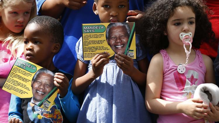 Children hold leaflets with pictures of former South African President Nelson Mandela while waiting outside of his house where he died, in Johannesburg