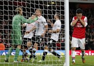 Fulham's goalkeeper Mark Schwarzer (L) celebrates saving the penalty taken by Arsenal's Mikel Arteta (R) during an English Premier League football match between Arsenal and Fulham at the Emirates Stadium in London. The match ended in a 3-3 draw