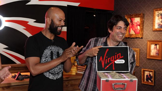 """Common and Virgin Mobile's Ron Faris with the proceeds from the Common benefit concert presented by Virgin mobile awarded to the Night Ministry at Virgin Mobile's """"From The Ground Up"""" event on Thursday, July 26, 2012 in Chicago, IL. (Photo by Barry Brecheisen/Invision for Virgin Mobile/AP Images)"""
