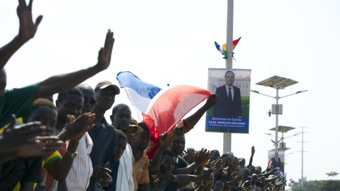 People wave flags as they line the streets to greet French President Francois Hollande in Conakry