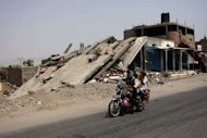 Yemeni men ride on a motorbike past a destroyed building after the Yemeni army drove Al-Qaeda fighters out of Jaar on June 15. Yemen's success in ousting Al-Qaeda from its southern strongholds this month has cemented President Abdrabuh Mansur Hadi's credibility, but analysts warn more challenges lie ahead for the new leader