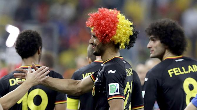 Belgium's Nacer Chadli, left, is congratulated by a teammate following Belgium's 1-0 victory over South Korea to Belgium during the group H World Cup soccer match between South Korea and Belgium at the Itaquerao Stadium in Sao Paulo, Brazil, Thursday, June 26, 2014