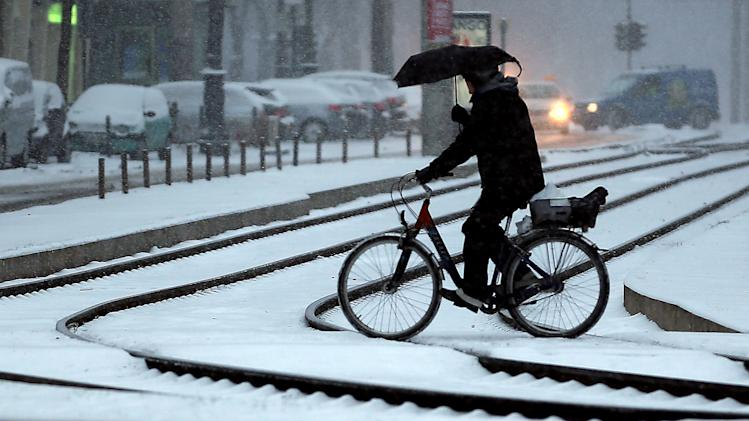 A cyclist holds an umbrella as he crosses tracks during snowfalls in Cologne, Germany, Tuesday, March 12, 2013. Fresh snow fell in wide oparts of Germany. (AP Photo/dpa, Oliver Berg)