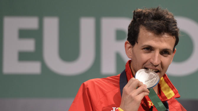 Spain's silver medalist Juan Carlos Higuero bites his medal during the medal ceremony for the men's 3000m at the Athletics Indoors European Championships in Gothenburg, Sweden, Saturday, March 2, 2013. (AP Photo/Martin Meissner)