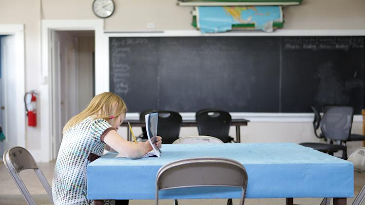 In this Tuesday, April 30, 2013 , photo, Polaris School student, Shelby Schrepfer practices her handwriting before recess in Polaris, Montana. She is one of four students at the rural school. (AP Photo/Kathryn Haake)