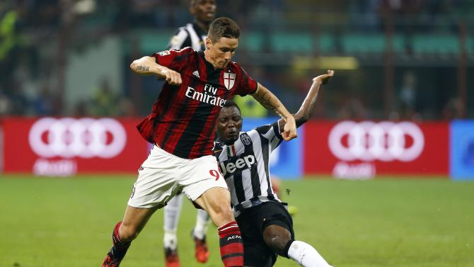 AC Milan's Torres challenges Juventus' Asamoah during their Italian Serie A soccer match at the San Siro stadium in Milan