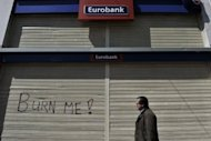 A man walks past a closed bank during a strike in Athens, 2011. European Union finance ministers struggled Wednesday to reach a deal on rules to shelter banks from future crises, as Britain and Sweden fought for the power to impose tougher defences