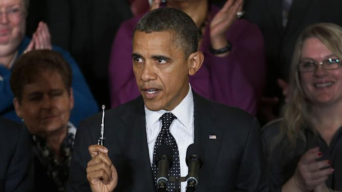 President Barack Obama holds up a pen as he speaks about the economy and the deficit, Friday, Nov. 9, 2012, in the East Room of the White House in Washington. (AP Photo/Carolyn Kaster)