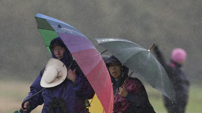 Spectators stand in the rain during the final day of the Women's British Open golf championships at Royal Liverpool Golf Club, Hoylake, England, Sunday Sept. 16, 2012.  (AP Photo/Jon Super)