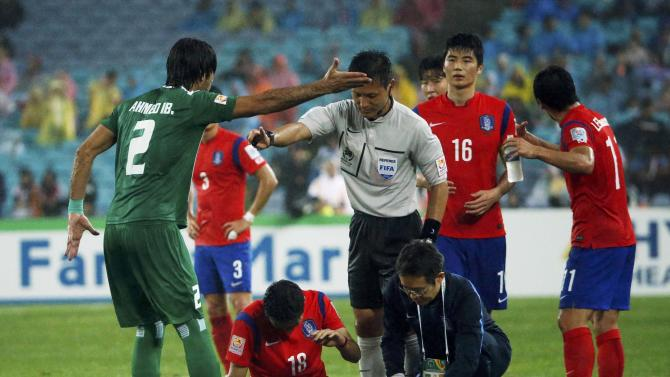 Iraq's Ahmed Ibrahim argues with referee Ryuji Sato of Japan as South Korea's Lee Jeong-hyeop receives medical treatment during their Asian Cup semi-final soccer match at the Stadium Australia in Sydney
