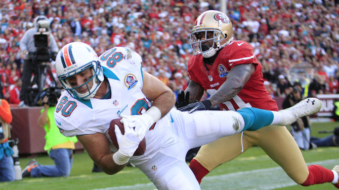 Miami Dolphins tight end Anthony Fasano falls into the end zone for a touchdown on a three-yard pass quarterback Ryan Tannehill as San Francisco 49ers strong safety Donte Whitner, right, looks on during the fourth quarter of an NFL football game in San Francisco, Sunday, Dec. 9, 2012. (AP Photo/Ben Margot)