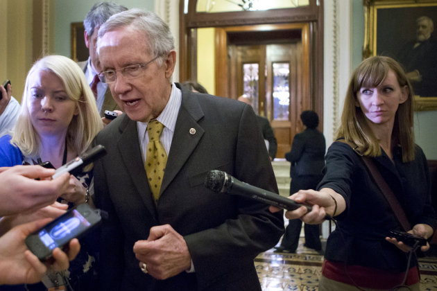 Senate Majority Leader Harry Reid, D-Nev., walks to a closed-door meeting with fellow Democrats as he and Senate Minority Leader Mitch McConnell, R-Ky., work to negotiate a legislative path to avoid the so-called &quot;fiscal cliff,&quot; at the Capitol in Washington, Sunday, Dec. 30, 2012. Senate and House leaders rushed to assemble a last-ditch agreement to stave off middle-class tax increases and possibly delay steep spending cuts in an urgent attempt to find common ground after weeks of gridlock. (AP Photo/J. Scott Applewhite)