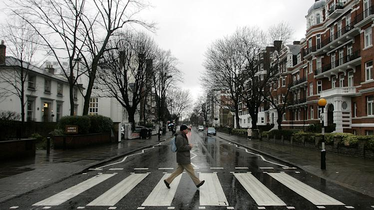 "FILE - In this file photo taken Feb. 16, 2010, a man walks on the zebra crossing  made famous from the album cover of The Beatles' 'Abbey Road' in front of Abbey Road Studios, seen at left, in London. It's a mystery tour, but it's hardly magical. More than nine miles from the striped crosswalk made famous by the Beatles album ""Abbey Road,"" this drab transit station in east London keeps drawing confused fans of the Fab Four into unwanted jaunts through a gritty, industrial area just south of London' Olympic Stadium. Abbey Road Station has no relation to the Beatles' Abbey Road Studios, the birth place of the eponymous album and a London tourist landmark. The glass-and-metal station is wedged between a train depot, warehouses, and gloomy public housing projects, a world away from the leafy, suburban street pictured on the album's cover.  (AP Photo/Akira Suemori, File)"