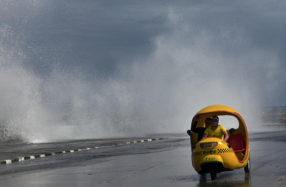 A man drives his Coco-taxi as a wave crashes against the Malecon after the passing of Hurricane Sandy in Havana, Cuba, Thursday, Oct. 25, 2012.  Hurricane Sandy blasted across eastern Cuba on Thursday as a potent Category 2 storm and headed for the Bahamas after causing at least two deaths in the Caribbean. (AP Photo/Ramon Espinosa)