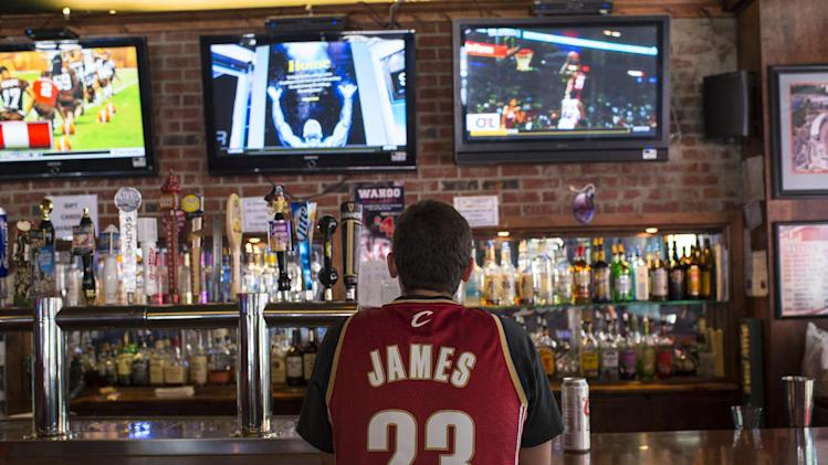A Cleveland Cavaliers fan wearing a Lebron James jersey watches news coverage of James' return to Cleveland in downtown Cleveland, Ohio, on July 11, 2014