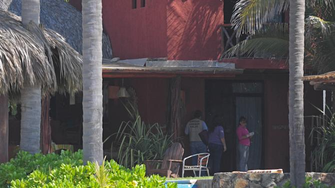 Police investigators work at a home after masked, armed men broke into the home in Acapulco, Mexico, Tuesday Feb. 5, 2013. According to the mayor of Acapulco, five masked men burst into this house that Spanish tourists had rented on the outskirts of Acapulco, in a low-key area near the beach, and held a group of six Spanish men and one Mexican woman at gunpoint, while they raped the six Spanish women before dawn on Monday. (AP Photo/Bernandino Hernandez)
