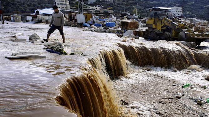 Palestinians cross a road flooded and swept away by heavy rains in the northern West Bank village of Kabatyeh, Wednesday, Jan. 9, 2013. A Palestinian official says the fiercest storm to hit the area in a decade has claimed the lives of two West Bank women who drowned after their car was caught in a flash flood unleashed by torrential rains. (AP Photo/Mohammed Ballas)