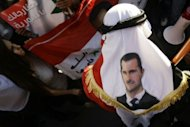 A man wears a head dress with an image of President Bashar al-Assad during a demonstration in support of the embattled leader in Damascus