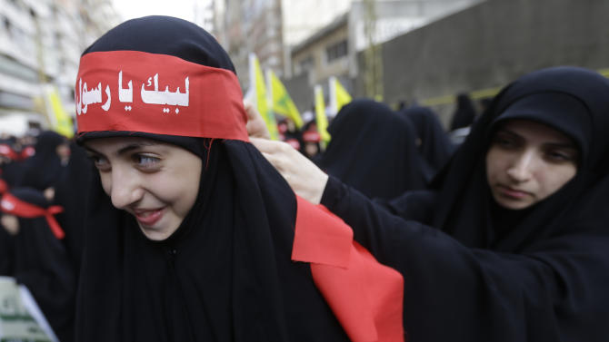 """A veiled Hezbollah supporters ties a banner on her friend's forehead, that reads in Arabic, """"At your service God's prophet,"""" during a rally denouncing an anti-Islam film that has provoked a week of unrest in Muslim countries worldwide, in the southern suburb of Beirut, Lebanon, Monday Sept. 17, 2012. Hezbollah's leader Hassan Nasrallah, not shown, who does not usually appear in public for fear of assassination, called for Monday's protests in Beirut, saying the U.S. must be held accountable for the film because it was produced in America. (AP Photo/Hussein Malla)"""