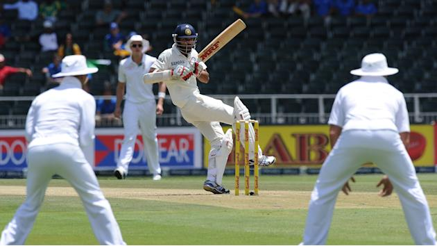 India's batsman Shikhar Dhawan (C) is in action on the 1st day of the cricket Test Match South Africa vs India at  Wanderers Stadium in Johannesburg on December 18, 2013. AFP PHOTO/ Str