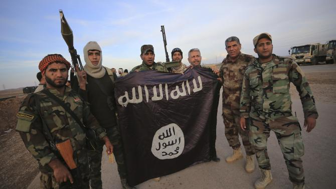 Iraqi Shi'ite fighters pose with an Islamic State flag which they pulled down on the front line in Jalawla