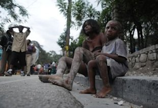 AP Photo/Jorge Cruz: Injured people sit along Delmas Road a day after the earthquake hit Port-au-Prince, Haiti.