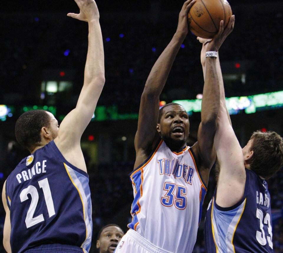 Oklahoma City Thunder forward Kevin Durant (35) goes to the basket in between Memphis Grizzlies Tayshaun Prince (21) and Marc Gasol (33) during the first quarter of Game 1 of their Western Conference Semifinals NBA basketball playoff series in Oklahoma City, Sunday, May 5, 2013.  (AP Photo/Alonzo Adams)